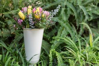 Vaso con fiori colorati e sfondo vegetazione