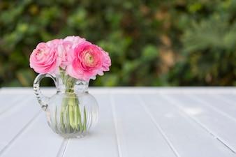 Vaso di vetro con fiori in toni rosa