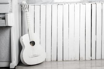 Vecchia chitarra acustica appoggiata contro la parete di legno bianca