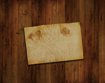 Vecchio pezzo di carta su una parete di legno del grunge