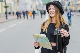 Viaggiatore femminile con la mappa e il binocolo