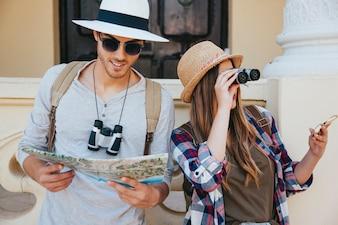 Viaggiatori persi con binocolo, mappa e occhiali da sole