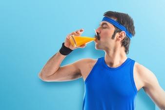 Vintage sportman bere succo d'arancia su sfondo colorato