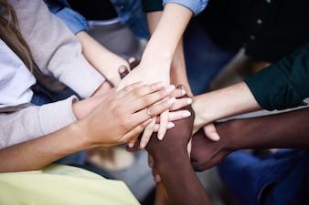 Vista dall'alto dei giovani che mettono le mani insieme.