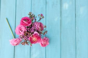 Vista dall'alto di fiori in toni rosa sulla superficie blu
