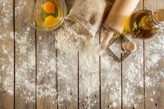 Vista dall'alto di superficie di legno con farina, uova e mattarello