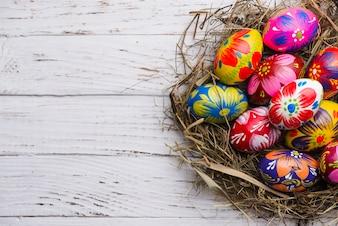 Vista dall'alto di superficie di legno con le uova di Pasqua dipinte