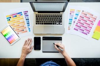 Vista dall'alto di un giovane graphic designer che lavora su un computer desktop e usando alcuni campioni di colore, vista dall'alto.