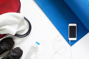 Vista frontale del concetto di yoga con bottiglia di acqua, scarpe da ginnastica, asciugamano, borsa e smartphone sulla stuoia yoga blu su sfondo bianco, isolato su bianco con copia sapce