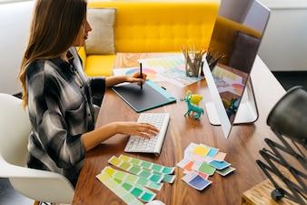 Vista laterale del graphic designer che lavora sul computer