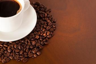 Vista parziale della tazza di caffè e dei fagioli sul tavolo di legno