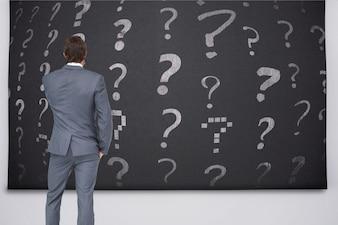 Vista posteriore di uomo d'affari guardando i punti interrogativi