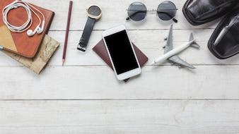 Vista superiore accessi per viaggiare concept.White telefono cellulare e cuffie su background.airplane di legno, mappa, passaporto, orologio sul tavolo di legno.