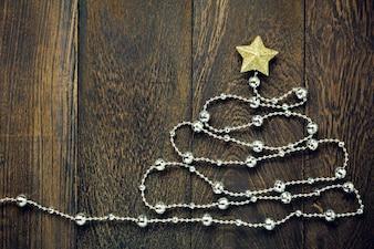 Vista superiore Christmas background.Fir albero da decorazioni natalizie, stella d'oro di Natale e clothesline dei gioielli sullo sfondo della tabella di legno con spazio di copia.