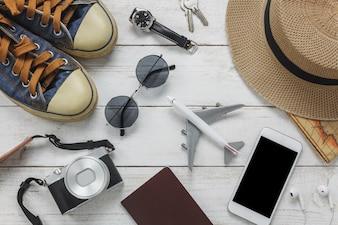 Vista superiore donne accessori per viaggiare concept.White telefono cellulare e cuffie su background.airplane di legno, cappello, passaporto, orologio, occhiali da sole sul tavolo di legno.