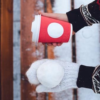 Womn tiene la palla di neve a mano in guanto bianco e tazza di carta rossa in un altro
