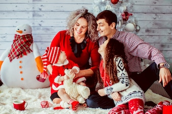 A família vestida de fantasia apresenta antes da árvore de Natal branca
