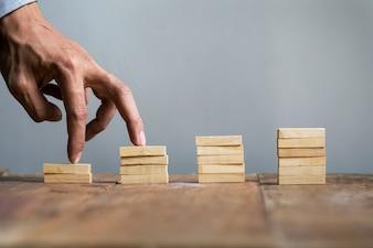 A mão compara pessoa de negócios pula uma escada de brinquedo para o sucesso, conceito de negócio