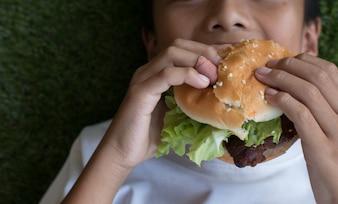 A mão do menino segurando um hambúrguer