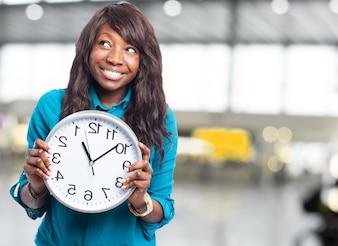 A menina alegre segurando um relógio e olhando para cima
