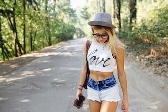 A menina loura com shorts em uma estrada