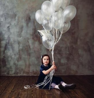 A menina pequena senta-se no assoalho e mantem ballons no quarto