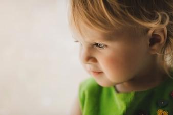 A menina pequena senta-se no quarto