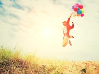 A menina que salta na praia com balões