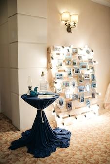 A mesa azul fica diante da parede com fotos e luzes