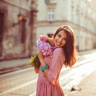 A mulher segura o ramo posando bem na rua matinal