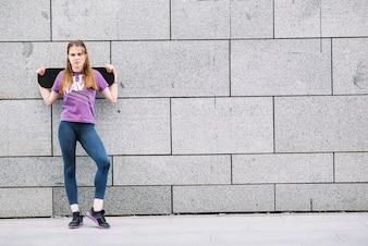 A mulher segura um skate de pé na frente de uma parede cinza