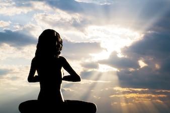 A silhueta da mulher praticando yoga