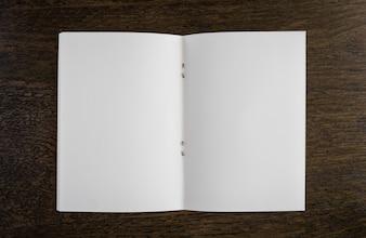 Abra o livro branco sobre uma mesa de madeira