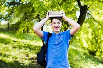 Adolescente alegre com livros na cabeça