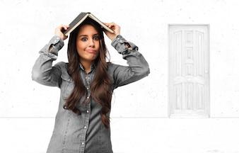Adolescente alegre que cobre sua cabeça com um livro