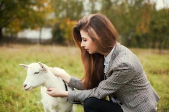 Adolescente com uma cabra ao ar livre