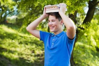 Adolescente feliz com livros na cabeça