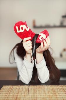 Adolescente triste segurando um coração partido