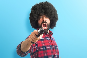 Afro homem atirando com uma pistola em fundo colorido