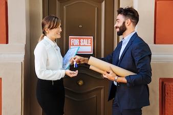 Agente imobiliário e mulher de negócios trocando chaves