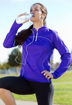 Água bebendo da mulher consideravelmente nova após o corredor.