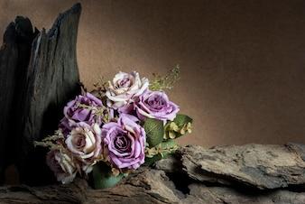 Ainda vida com rosas roxas e madeira