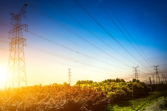 Ajuste do sol atrás da silhueta das torres de eletricidade
