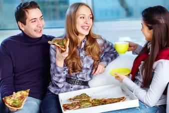 Amigos comendo pizza e beber café