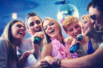 Amigos felizes que cantam karaoke junto