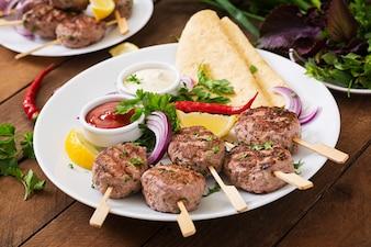 Apetitoso kofta kebab (meatballs) com molho e tacadas de tortilhas em um prato branco