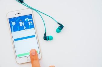 Aplicativo do Facebook no telefone, no dedo e nos fones de ouvido