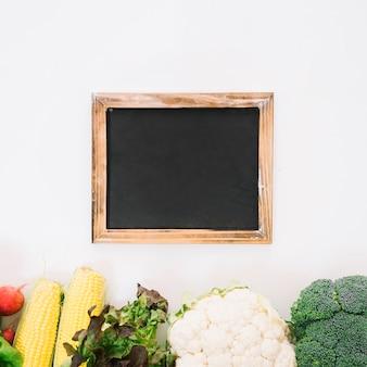 Ardósia com legumes no fundo