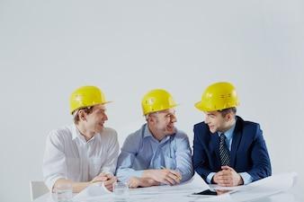 Arquitetos com capacetes amarelos rindo
