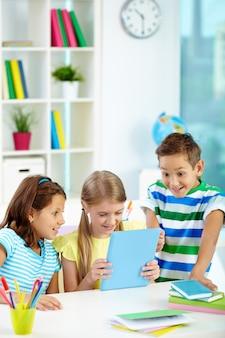 As crianças se divertindo com uma tabuleta digital